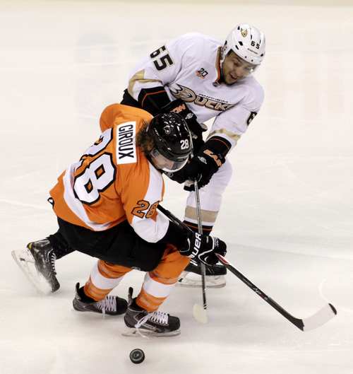 Anaheim Ducks' Emerson Etem (65) and Philadelphia Flyers' Clude Giroux (28) fight for puck control in the first period of an NHL hockey game, Tuesday Oct. 29, 2013, in Philadelphia.  (AP Photo/H. Rumph Jr)
