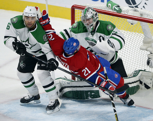 Montreal Canadiens right wing Brian Gionta (21) runs into Dallas Stars goalie Kari Lehtonen (32) and defenseman Trevor Daley (6) during the second period of an NHL hockey game Tuesday, Oct. 29, 2013, in Montreal. (AP Photo/The Canadian Press, Ryan Remiorz)