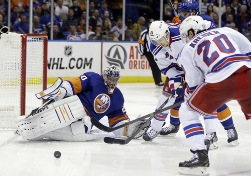 New York Islanders goalie Evgeni Nabokov (20) protects the goal from New York Rangers' Derek Stepan (21) and Chris Kreider (20) during the third period of an NHL hockey game Tuesday, Oct. 29, 2013, in Uniondale, N.Y. The Rangers won the game 3-2. (AP Photo/Frank Franklin II)