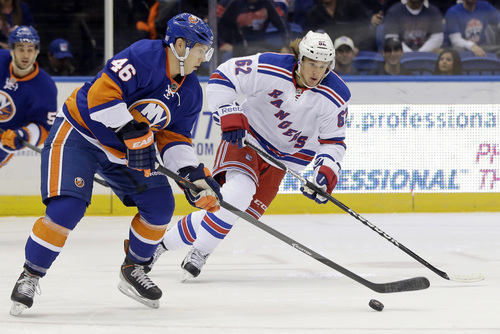 New York Islanders' Matt Donovan (46) and New York Rangers' Carl Hagelin (62) fight for control of the puck during the first period of an NHL hockey game Tuesday, Oct. 29, 2013, in Uniondale, N.Y.  (AP Photo/Frank Franklin II)