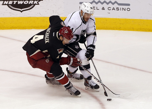 Phoenix Coyotes' Zbynek Michalek (4), of the Czech Republic, battles Los Angeles Kings' Dwight King (74) for the puck during the second period of an NHL hockey game on Tuesday, Oct. 29, 2013, in Glendale, Ariz. (AP Photo/Matt York)