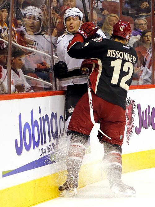 Phoenix Coyotes' Paul Bissonnette (12) checks Los Angeles Kings' Drew Doughty into the boards during the first period of an NHL hockey game, Tuesday, Oct. 29, 2013, in Glendale, Ariz. (AP Photo/Matt York)