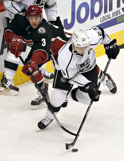 Phoenix Coyotes' Keith Yandle (3) battles Los Angeles Kings' Dustin Brown for the puck during the third period of an NHL hockey game onTuesday, Oct. 29, 2013, in Glendale, Ariz. The Coyotes won 3-1. (AP Photo/Matt York)
