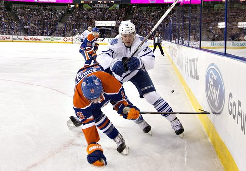 Toronto Maple Leafs winger Carter Ashton (37) checks Edmonton Oilers defenseman Justin Schultz (19) during the first period of an NHL hockey game in Edmonton, Alberta, Tuesday, Oct. 29, 2013. (AP Photo/The Canadian Press, Jason Franson)