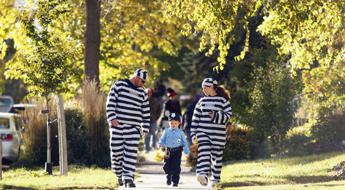 In this Saturday, Oct. 26, 2013 photo, Dylan, left, and Michelle Porterfield, of West Bend, Wis., walk with their son, Hunter, 4, dressed as a police officer, while trick-or-treating in West Bend. Parents can now use apps to digitally accompany their trick-or-treaters on Halloween night. (AP Photo/West Bend Daily News, John Ehlke)