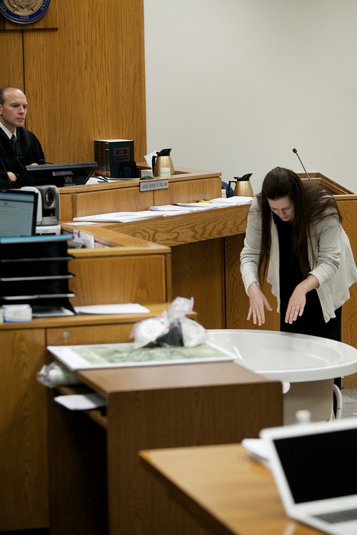 Mark Johnston  |  Pool  Alexis Somers demonstrates her father Martin MacNeill's own demonstration during testimony at 4th District Court in Provo Wednesday, Oct. 30, 2013. Martin MacNeill is charged with murder for allegedly killing his wife Michele MacNeill in 2007, who was found in a bathtub at the family's home. During her testimony, Somers demonstrated her father's own demonstration of the position he told her he found her deceased mother.