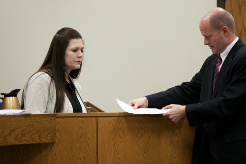 Mark Johnston  |  Pool  Alexis Somers is handed documents by Chad Grunander, Utah County prosecutor, while testifying at the trial of her father Martin MacNeill at 4th District Court in Provo Wednesday, Oct. 30, 2013. Martin MacNeill is charged with murder for allegedly killing his wife Michele MacNeill in 2007.