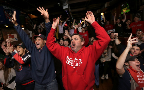 Boston Red Sox fan George Moriarty, of Agawam, Mass., center, cheers with others in a bar near Fenway Park as the Red Sox score in the fourth inning of Game 6 of baseball's World Series against the St. Louis Cardinals on Wednesday, Oct. 30, 2013, in Boston. (AP Photo/Steven Senne)