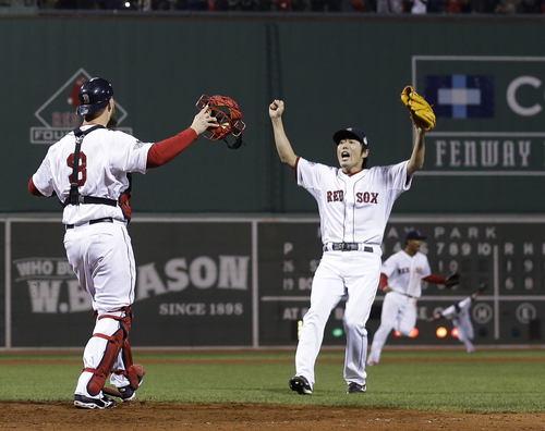 Boston Red Sox relief pitcher Koji Uehara and catcher David Ross celebrate after getting St. Louis Cardinals' Matt Carpenter to strike out and end Game 6 of baseball's World Series Wednesday, Oct. 30, 2013, in Boston. The Red Sox won 6-1 to win the series. (AP Photo/David J. Phillip)
