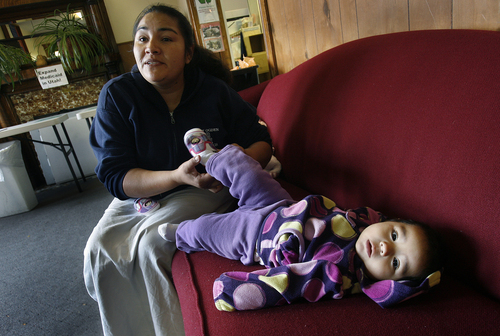 Scott Sommerdorf   |  The Salt Lake Tribune Mardalia Perez tends to her daughter Elianai, 6 months, as she waits at the Crossroads Urban Center food pantry, Wednesday, October 30, 2013. They were there for food that will get them through the month after their food stamps run out. The Food Stamp program (Supplemental Nutrition Assistance Program -- SNAP) will be rolled back to 2008 levels on Nov. 1. This means cuts of $36 per month for a family of four now on the program.