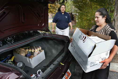 Scott Sommerdorf   |  The Salt Lake Tribune Mardalia Perez, background, is helped by her sister as they load food they had gotten at the Crossroads Urban Center food pantry, Wednesday, October 30, 2013. They were there for food that will get them through the month after their food stamps run out. The Food Stamp program (Supplemental Nutrition Assistance Program -- SNAP) will be rolled back to 2008 levels on Nov. 1. This means cuts of $36 per month for a family of four now on the program.