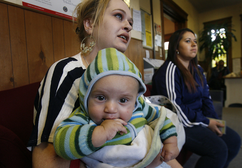 Scott Sommerdorf   |  The Salt Lake Tribune Karman Grover holds her grandson Elias, 5 months, as her daughter Eloria sits to the right at the Crossroads Urban Center food pantry, Wednesday, October 30, 2013. They are there for food that will get them through the month after their food stamps run out. The Food Stamp program (Supplemental Nutrition Assistance Program -- SNAP) will be rolled back to 2008 levels on Nov. 1. This means cuts of $36 per month for a family of four now on the program.