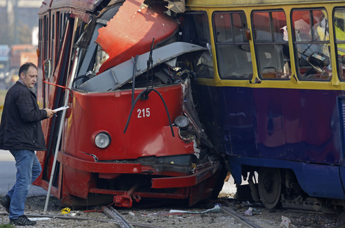 Police officers investigate the crash site of two trams in the Bosnian capital of Sarajevo, on Friday, Nov. 1, 2013. Authorities say some 45 people were injured when one tram slammed into another at a busy downtown intersection in Sarajevo. Irfan Nefic, the spokesman for the Sarajevo police, said Friday court experts are still investigating the causes of the accident. He said so far none of the injuries of the approximately 45 people were life threatening. (AP Photo/Amel Emric)