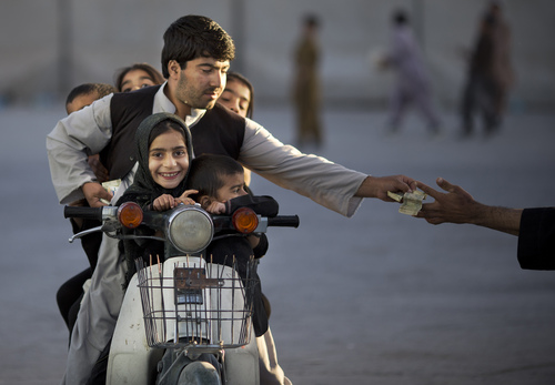 An Afghan man with his five children on his motorbike pays money to enter a park in Kandahar, southern Afghanistan, Friday, Nov 1, 2013. On Fridays, the Islamic day of rest and prayer, children and their families traditionally gather in one of the few parks. (AP Photo/Anja Niedringhaus)