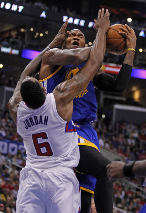 Los Angeles Clippers center DeAndre Jordan (6) blocks a shot by Golden State Warriors forward Marreese Speights, top, in the third quarter during an NBA basketball game on Thursday, Oct. 31, 2013, in Los Angeles. The Clippers won the game 126-115.  (AP Photo/Alex Gallardo)