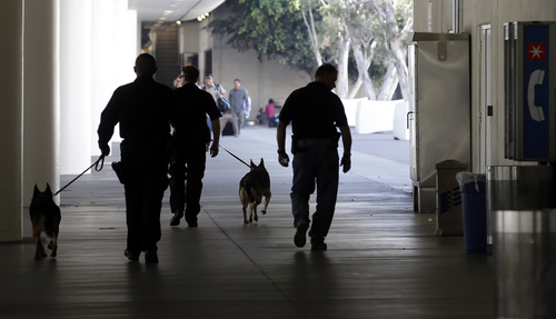 Police check the area around Terminal 1 at Los Angeles International Airport on Friday, Nov. 1, 2013. A gunman armed with a semi-automatic rifle opened fire at the airport on Friday, killing a Transportation Security Administration employee and wounding two other people. Flights were disrupted nationwide. (AP Photo/Reed Saxon)