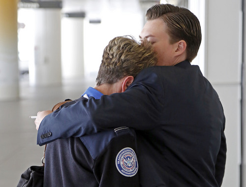 Transportation Security Administration employees hug outside Terminal 1 at Los Angeles International Airport on Friday, Nov. 1, 2013. A gunman armed with a semi-automatic rifle opened fire at Los Angeles International Airport on Friday, killing a TSA employee and wounding two other people. Flights were disrupted nationwide. (AP Photo/Reed Saxon)