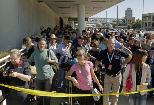 Passengers evacuated from Terminal 1 wait outside Los Angeles International Airport on Friday Nov. 1, 2013. Shots were fired Friday at Los Angeles International Airport, prompting authorities to evacuate a terminal and stop flights headed for the city from taking off from other airports. (AP Photo/Reed Saxon)