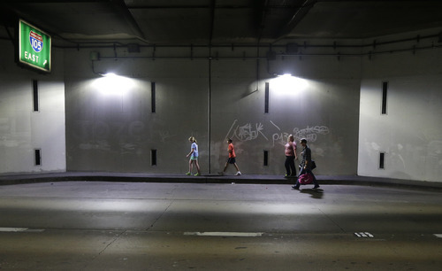Matt McGuinness, right, walks in a tunnel with his family as they leave Los Angeles International Airport, Friday, Nov. 1, 2013. From left are Ella, Luke and Alicia. A gunman with a semi-automatic weapon opened fire in Terminal 3 and was later taken into custody. Flights were disrupted nationwide. (AP Photo/Gregory Bull)