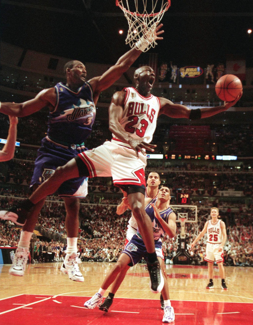 Tribune file photo  The Chicago Bulls' Michael Jordan goes up and under Utah Jazz forward Karl Malone as he drives to the hoop during the third quarter of Game 2 in the NBA Finals on June 4, 1997, in Chicago.
