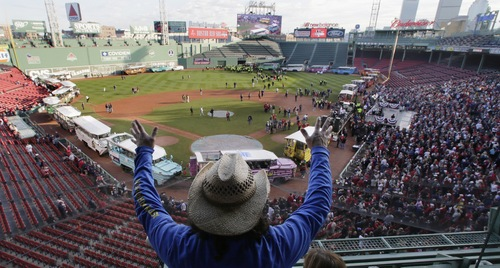 Carlos Arredondo raises his arms as he waves to fans at Fenway Park in advance of the Boston Red Sox's championship parade in celebration of the baseball team's World Series win, Saturday, Nov. 2, 2013, in Boston. (AP Photo/Charles Krupa)