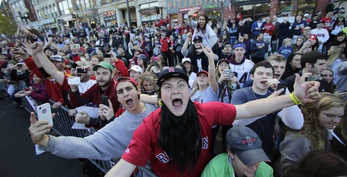Boston Red Sox fans celebrate during a parade in celebration of the baseball team's World Series victoru, Saturday, Nov. 2, 2013, in Boston. (AP Photo/Charles Krupa)