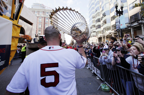Boston Red Sox's Jonny Gomes carries the 2013 World Series trophy and a team jersey to the finish line of the Boston Marathon, in honor of those affected by the bombings, as they stopped the parade in celebration of the baseball team's World Series win, Saturday, Nov. 2, 2013, in Boston. (AP Photo/Charles Krupa)