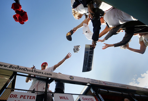 Fans at Fenway Park reach out to Boston Red Sox's Will Middlebrooks, left, who stands in a duck boat ready to celebrate their World Series baseball championship in a rolling rally in Boston, Saturday, Nov. 2, 2013. (AP Photo/Elise Amendola)