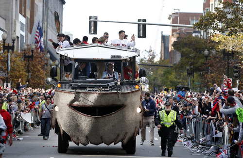 Boston Red Sox relief pitchers Junichi Tazawa, far left, and Koji Uehara, far right, wave to fans from a duck boat as they celebrate their World Series baseball championship in a rolling rally in Boston, Saturday, Nov. 2, 2013. (AP Photo/Elise Amendola)