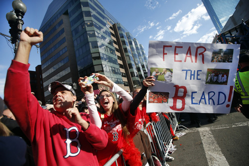 Boston Red Sox fans cheer as they watch a rolling rally of duck boats pass by during a celebration of the team's World Series baseball championship in Boston, Saturday, Nov. 2, 2013. (AP Photo/Elise Amendola)