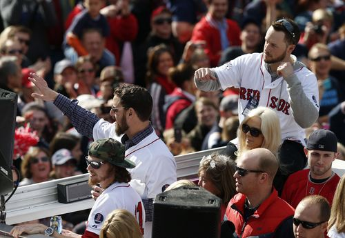Boston Red Sox's Clay Buchholz, left, John Lackey, second from left, and Daniel Nava, top right, wave from a Duck Boat during a victory parade celebrating the team's third World Series title since 2004, Saturday, Nov. 2, 2013, in Boston. (AP Photo/Michael Dwyer)
