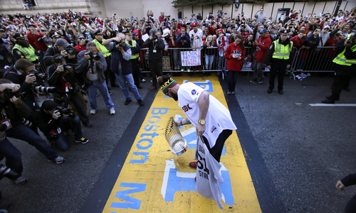 Boston Red Sox's Jonny Gomes puts the 2013 World Series trophy and a team jersey on the finish line of the Boston Marathon, in honor of those affected by the bombings, as they stopped the parade in celebration of the baseball team's World Series win, Saturday, Nov. 2, 2013, in Boston. (AP Photo/Charles Krupa)