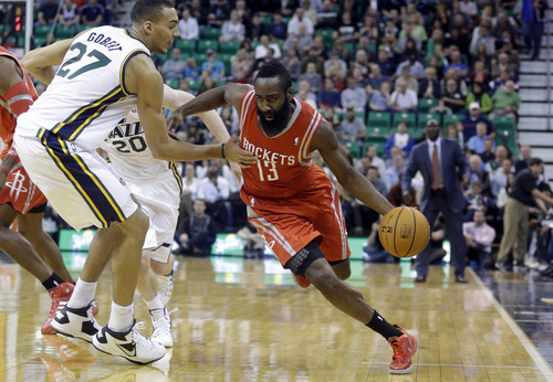 Houston Rockets' James Harden (13) drives around Utah Jazz's Rudy Gobert (27), of France, in the first quarter during an NBA basketball game Saturday, Nov. 2, 2013, in Salt Lake City.  (AP Photo/Rick Bowmer)