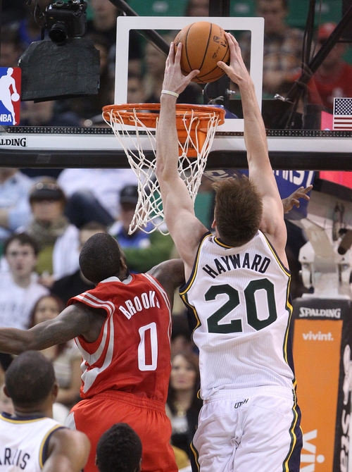 Utah Jazz's Gordon Hayward (20) dunks the ball over Houston Rockets' Aaron Brooks (0) in the second quarter during an NBA basketball game Saturday, Nov. 2, 2013, in Salt Lake City.  (AP Photo/Rick Bowmer)