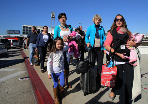 Passengers evacuate the Los Angeles International Airport on Friday Nov. 1, 2013, after shots were fired there, prompting authorities to evacuate a terminal and stop flights headed for the city from taking off from other airports. (AP Photo/Ringo H.W. Chiu)
