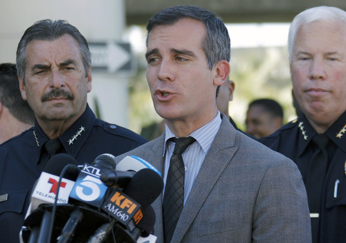 Los Angeles Police Chief Charlie Beck, left, joins Los Angeles Mayor Eric Garcetti, center, during a news conference at Los Angeles International Airport on Friday Nov. 1, 2013. A gunman armed with a semi-automatic rifle opened fire at Los Angeles International Airport on Friday, killing a Transportation Security Administration employee and wounding two other people. (AP Photo/Nick Ut)