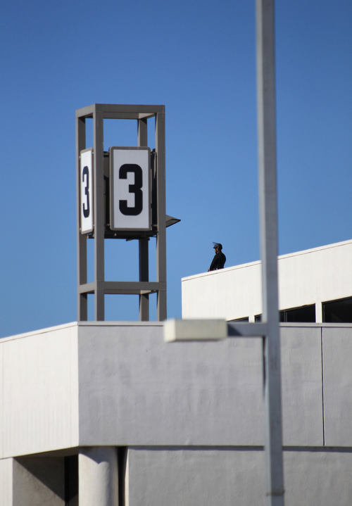 A policer officer stands guard atop Terminal 3 at Los Angeles International Airport on Friday Nov. 1, 2013. Shots were fired Friday at the airport, prompting authorities to evacuate a terminal and stop flights headed for the city from taking off from other airports. (AP Photo/Ringo H.W. Chiu)