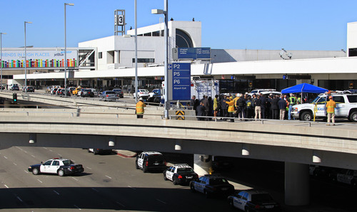 Police, emergency response vehicles and officials are positioned outside Terminal 3 at Los Angeles International Airport on Friday, Nov. 1, 2013. Shots were fired Friday at Los Angeles International Airport, prompting authorities to evacuate a terminal and stop flights headed for the city from taking off from other airports. (AP Photo/Ringo H.W. Chiu)