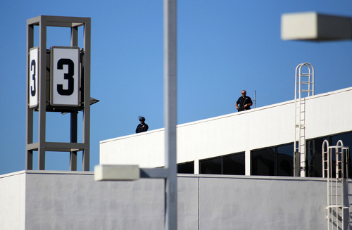 Police officers stand guard atop Terminal 3 at the Los Angeles International Airport on Friday Nov. 1, 2013. Shots were fired Friday at Los Angeles International Airport, prompting authorities to evacuate a terminal and stop flights headed for the city from taking off from other airports. (AP Photo/Ringo H.W. Chiu)