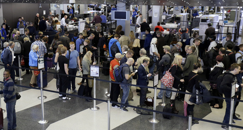 Travelers wait in line at a security check station at Chicago O'Hare International Airport on Friday, Nov. 1, 2013. A gunman armed with a semi-automatic rifle opened fire at Los Angeles International Airport on Friday, killing a Transportation Security Administration employee and wounding two other people. Flights were disrupted nationwide. (AP Photo/Nam Y. Huh)
