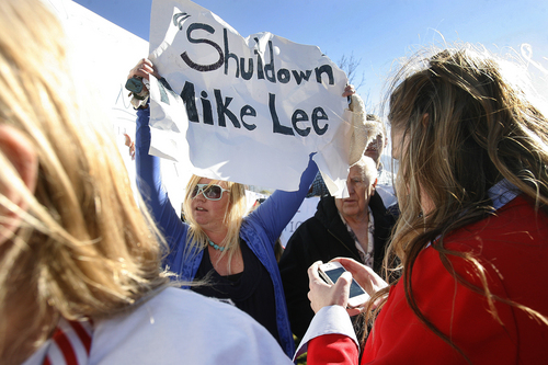 Scott Sommerdorf   |  The Salt Lake Tribune Anti-Lee demonstrator Melissa Walker along with a small group of others chant their disapproval of Sen. Mike Lee from the fringes of the rally held Saturday to show support for Lee in South Jordan.