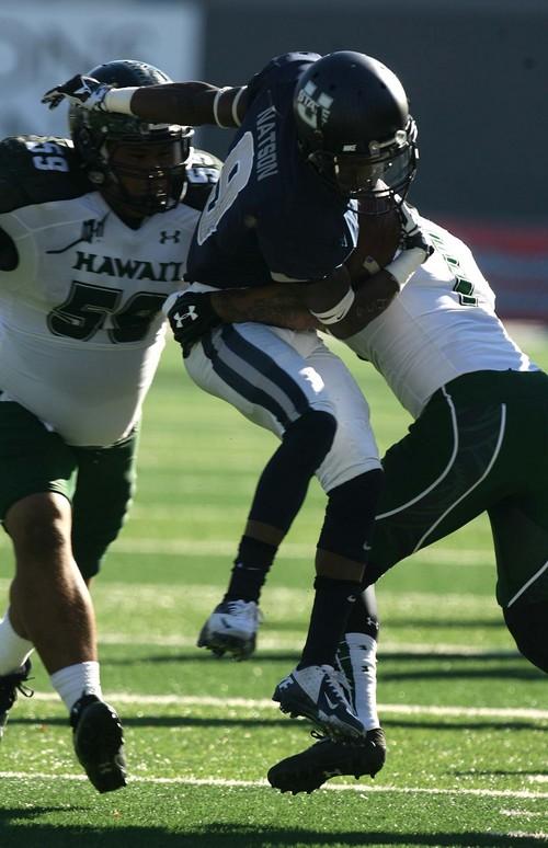 Leah Hogsten  |  The Salt Lake Tribune Utah State Aggies wide receiver Bruce Natson (9) is airborne before getting stopped by Hawaii Warriors defensive back Ne'Quan Phillips (1). Utah State University hosts Hawaii at Romney Stadium, Saturday, November 2, 2013.
