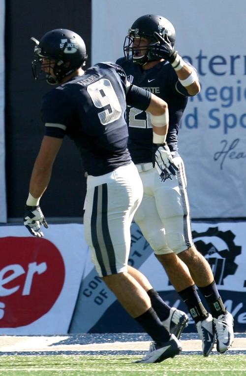 Leah Hogsten  |  The Salt Lake Tribune Utah State Aggies safety Brian Suite (21) celebrates his interception. Utah State University hosts Hawaii at Romney Stadium, Saturday, November 2, 2013.