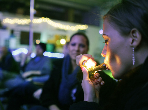 FILE - In this in Dec. 31, 2012 file photo, Rachel Schaefer of Denver smokes marijuana on the official opening night of Club 64, a marijuana-specific social club, where a New Year's Eve party was held,  in Denver. According to new guidance being issued Thursday, Aug. 29, 2013 to federal prosecutors across the country, the federal government will not make it a priority to block marijuana legalization in Colorado or Washington or close down recreational marijuana stores, so long as the stores abide by state regulations. (AP Photo/Brennan Linsley)