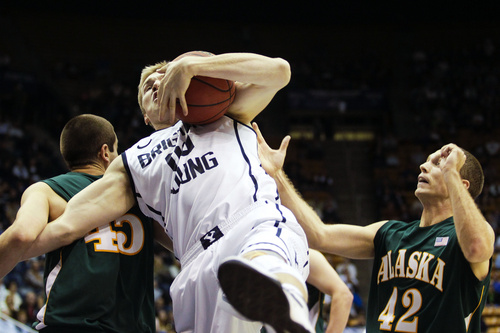 Brigham Young forward Eric Mika (00) brings in a rebound between Alaska-Anchorage's Jackson McTier (45) and Kyle Fossman (42) during an NCAA college basketball exhibition game Saturday, Nov. 2, 2013, in Provo, Utah. (AP Photo/Daily Herald, Alex Goodlett)