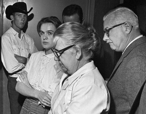 """FILE - In this Nov. 22, 1963 file photo, Marina Oswald, second left, stands with her mother-in-law, Marguerite Claverie Oswald, in the police station in Dallas where her husband, Lee Harvey Oswald is being held, accused in the assassination of President John F. Kennedy. In separate interviews with The Associated Press, Warren Commission staff counsel Burt Griffin and fellow staff counsel David Slawson pointed to a series of personal rejections behind Oswald's deadly action: Weeks after he made an unsuccessful attempt in Mexico City to get a visa to Cuba, his wife Marina rejected his attempts to reconcile their rocky marriage. It was during his visit, the night before the shooting, to the suburban Dallas home where his wifeand two young daughters were staying that he packed up his disassembled Mannlicher-Carcano rifle to take to work the next day, the Warren Commission determined. That next morning, he removed his wedding ring, left his money with his wife, and departed to carry out the assassination. """"If she had taken him back,"""" Slawson said, """"he wouldn't have done it."""" (AP Photo)"""
