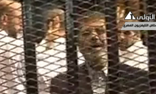 """This image made from video broadcast on Egyptian State Television shows ousted President Mohammed Morsi speaking from inside a mesh cage as he stands with other defendants during a court hearing at a police academy compound in Cairo, Egypt, Monday, Nov. 4, 2013. After four months in secret detention, Egypt's deposed Islamist president defiantly rejected a court's authority to try him Monday, saying he was the country's """"legitimate"""" leader and those that overthrew him should face charges instead. The trial was then adjourned until Jan. 8 after several interruptions.(AP Photo/Egyptian State Television via AP video)"""