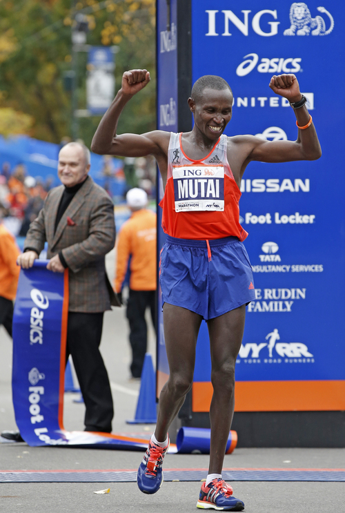 New York City Police Chief Raymond Kelly, left, watches as defending champion Geoffrey Mutai of Kenya gestures after winning the men's division of the the New York City Marathon, Sunday, Nov. 3, 2013, in New York. (AP Photo/Kathy Willens)
