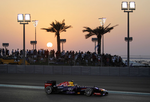Red Bull driver Sebastian Vettel of Germany steers his car during the Abu Dhabi Formula One Grand Prix at the Yas Marina racetrack in Abu Dhabi, United Arab Emirates, Sunday, Nov. 3, 2013. The moon crosses in front of the sun during a partial solar eclipse at background. (AP Photo/Kamran Jebreili)