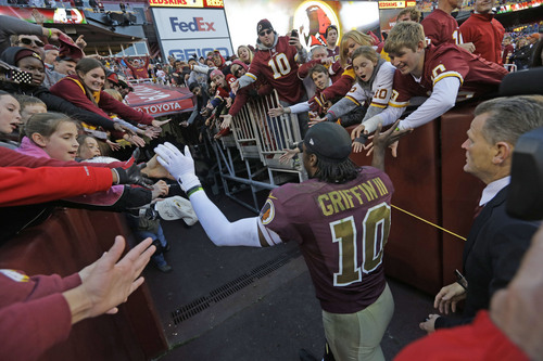 Washington Redskins quarterback Robert Griffin III is greeted by the fans has he leaves the field after an overtime victory over the San Diego Chargers in a NFL football game in Landover, Md., Sunday, Nov. 3, 2013. Washington defeated San Diego 30-24 in overtime. (AP Photo/Patrick Semansky)